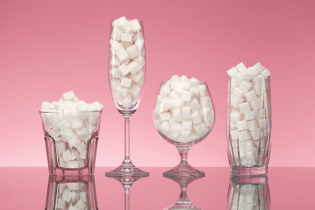 Foto de Sugar In Drinks. Glasses Full Of White Sugar Cubes. Close Up Of Transparent Glasswear With Refined Sugar On Pink Background. High Quality - Imagen libre de derechos