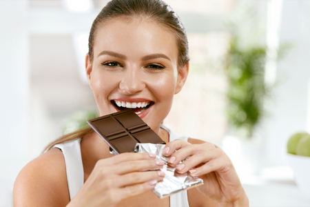Photo pour Woman Eating Chocolate. Beautiful Girl With Sweets. Portrait Of Happy Smiling Young Female Biting And Enjoying Chocolate Indoors.Food And Diet Concept. High Quality - image libre de droit