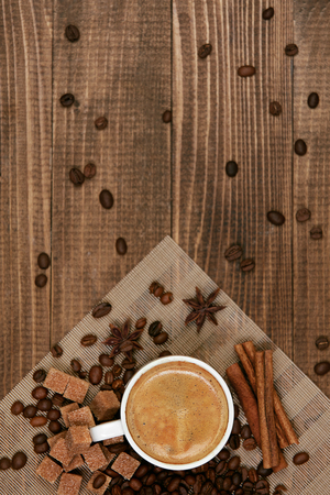 Foto de Coffee Drink. Cup Of Coffee On Wooden Table. Flat Lay Close Up Of Hot Beverage In White Mug On Plate And Coffee Beans On Wooden Background. Top View. High Quality Image. - Imagen libre de derechos