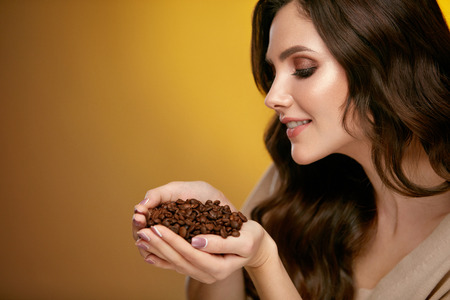 Foto de Coffee Beans. Beautiful Woman Smelling Coffee Beans. Attractive Smiling Female With Gorgeous Makeup On Beauty Face And Curly Brown Hair Holding Coffee Beans In Hands, Enjoying Aroma On Gold Background - Imagen libre de derechos