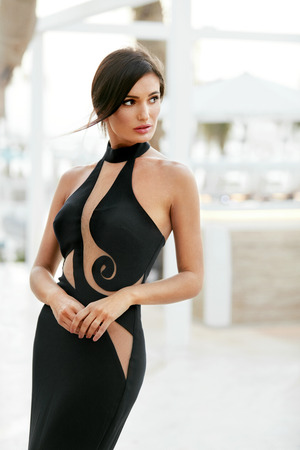 Photo for Women Style. Fashion Girl In Long Black Dress Posing Outdoors. Portrait Of Beautiful Fashionable Female Model In Glamourous Evening Dress With Elegant Hairstyle Posing Outdoors. High Quality Image. - Royalty Free Image