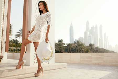 Foto de Fashion. Woman In Beautiful White Dress Outdoors On Street. Portrait Of Sexy Young Female Model Wearing Stylish Clothes Holding White Fashionable Hat At Luxury Resort In Summer. High Resolution. - Imagen libre de derechos