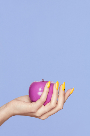 Photo for Nails Design. Female Hands With Colorful Nails Holding Apple On Violet Background. Close Up Of Woman Fingers With Fashion Orange Manicure Holding Purple Apple. High Quality Image. - Royalty Free Image
