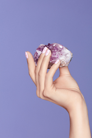 Photo pour Manicure. Hand With Stylish Nails Holding Purple Gemstone. Close Up Of Female Fingers With Pastel Manicure Holding Violet Precious Stone On Violet Background. High Quality Image. - image libre de droit