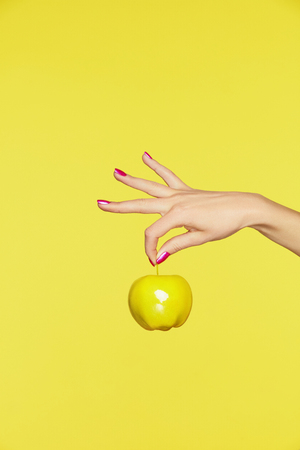 Foto de Nails Design. Female Hands With Colorful Nails Holding Apple On Yellow Background. Close Up Of Woman Fingers With Fashion Purple Manicure Holding Yellow Apple. High Quality Image. - Imagen libre de derechos
