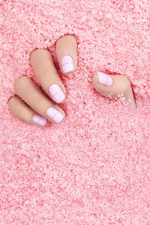 Photo pour Female Hands With Nails In Colorful Sea Salt. Close Up Of Woman Hand With White Manicure In Pink Sea Salt. High Quality Image. - image libre de droit