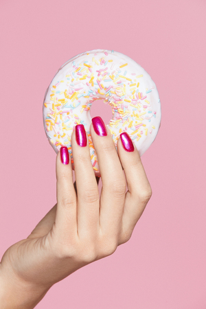 Photo pour Manicure. Hand With Pink Nails Holding Donut. Close Up Of Female With Beauty Pink Manicure Holding Sweet Donut In Hand On Pink Background. High Quality Image. - image libre de droit
