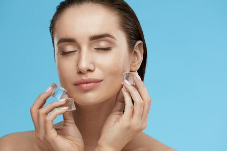 Foto de Face Skin Care. Woman Applying Ice Cubes. Beautiful Smiling Girl Doing Icing Facial Treatment On Fresh Healthy Skin. High Quality - Imagen libre de derechos