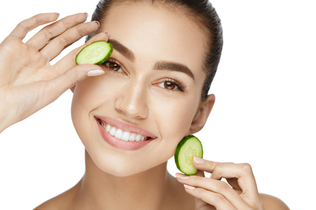Photo for Beauty Woman Face With Fresh Skin In Spa. Female Removing Dark Circles With Cucumber Slices On White Background. High Resolution. - Royalty Free Image