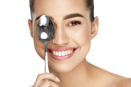 Photo for Eye Skin Care. Beautiful Woman With Healthy Skin Holding Cold Spoon Near Eye On White Background. High Resolution. - Royalty Free Image