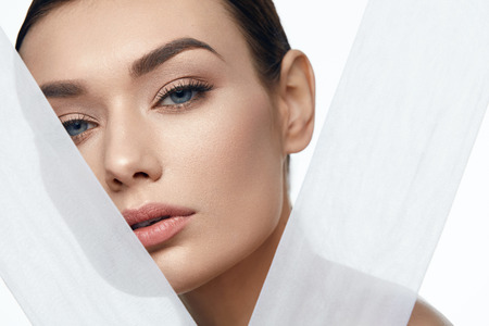 Photo pour Face Skin Beauty. Beautiful Woman With Natural Makeup, Healthy Skin With White Pieces Of Fabric. High Resolution. - image libre de droit