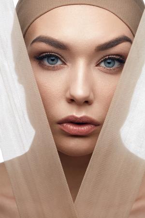 Foto de Beauty Woman Face With Even Skin Tone Foundation With Pastel Pieces Of Fabric. High Resolution. - Imagen libre de derechos