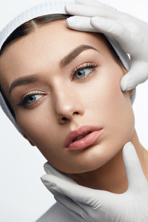 Photo pour Plastic Surgery. Hands Touching Beautiful Woman Face On White Background. High Resolution. - image libre de droit