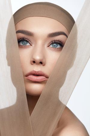 Foto de Skin Care Beauty. Woman With Beautiful Face, Natural Makeup And With Beige Fabric. High Resolution. - Imagen libre de derechos