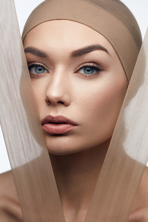 Foto de Beauty Woman Face With Even Skin Tone On Face With Pastel Pieces Of Fabric. High Quality Image. - Imagen libre de derechos