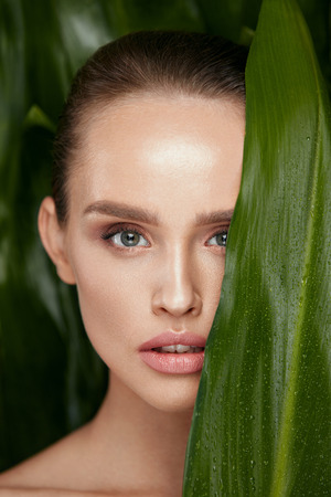 Photo pour Skin Care. Beautiful Woman With Natural Makeup And Healthy Facial Skin Holding Green Leaves. High Quality Image. - image libre de droit