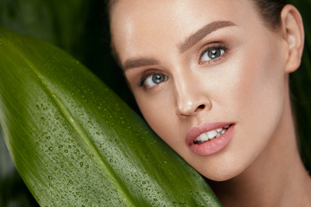 Photo pour Beauty Woman Face With Healthy Skin And Natural Makeup With Green Plant On Jungle Background. High Resolution. - image libre de droit