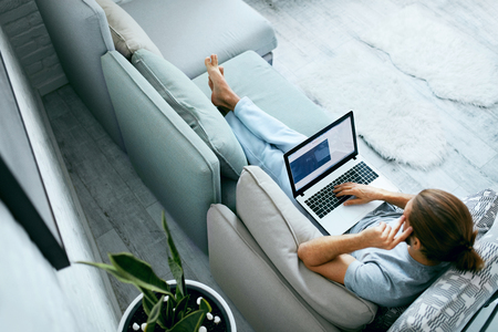 Photo pour Young Man With Laptop At Home. Handsome Male Wearing Home Clothes Working At Computer, Sitting On Sofa. High Resolution. - image libre de droit