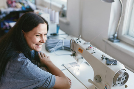 Photo for Female Working On Sewing Machine. Portrait Of Woman Tailor Sewing Clothes Sitting At Table - Royalty Free Image
