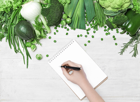 Photo for Diet Plan. Female Hand Writing In Notebook Near Fresh Green Vegetables On White Table. High Resolution. - Royalty Free Image