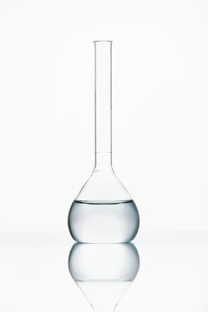 Foto de Laboratory Glass With Transparent Chemical Liquid On White Background. High Resolution. - Imagen libre de derechos
