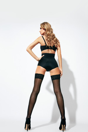 Foto de Stockings. Back View Of Sexy Young Blonde Female With Long Sexy Legs Wearing Black Underwear. High Resolution. - Imagen libre de derechos