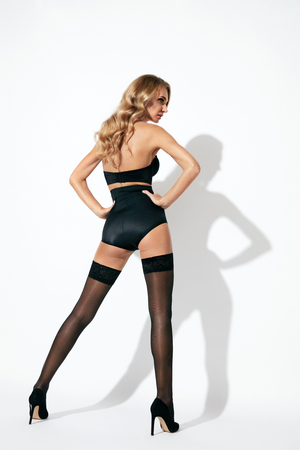 Photo pour Stockings. Back View Of Sexy Young Blonde Female With Long Sexy Legs Wearing Black Underwear. High Resolution. - image libre de droit