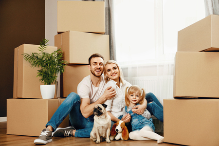Photo pour Family Moving Home. Happy People With Child And Dog Hugging While Sitting On Floor In New House. High Resolution. - image libre de droit