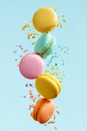 Photo pour Macaron Dessert. Colorful Macaroons Flying. French Dessert In Motion Falling On Blue Background. High Resolution - image libre de droit