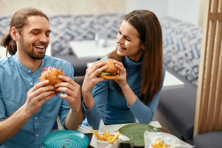 Photo for People Having Dinner, Eating Burgers At Cafe. Friends Eating Fast Food In Restaurant. High Resolution. - Royalty Free Image
