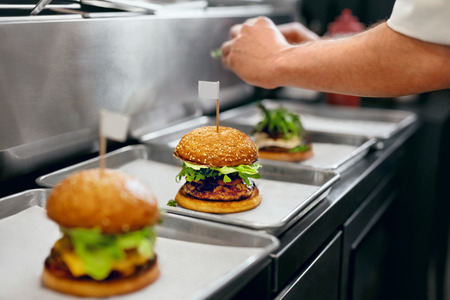 Foto de Burger Restaurant. Closeup Chef Cooking Burgers In Kitchen. High Resolution. - Imagen libre de derechos