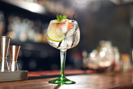 Photo for Cocktail Drink In Bar Close Up. Glass Of Gin Tonic Cocktail With Lime And Mint On Bar Counter. High Resolution - Royalty Free Image