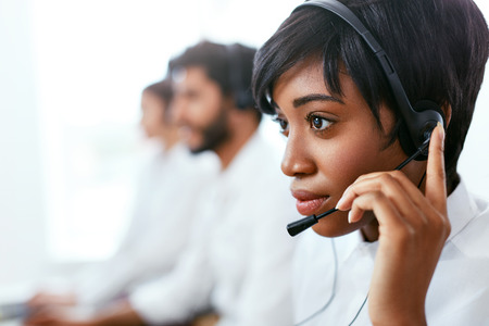 Photo pour Contact Center Operator Consulting Client On Hotline. Attractive Afro-American Woman Serving Customers In Call-Center. High Resolution - image libre de droit