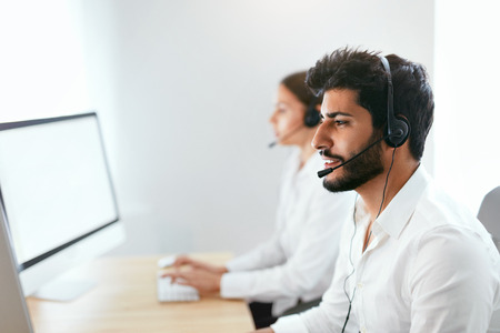 Foto de Contact Center Agent Consulting Customers Online. Man And Woman Working On Helpline In Call-Center. High Resolution - Imagen libre de derechos