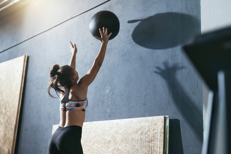 Photo pour Workout. Sport Woman Training With Crossfit Ball At Gym - image libre de droit
