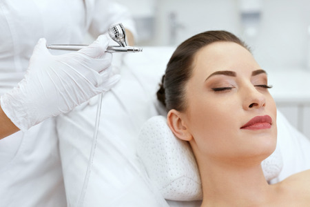 Foto de Beauty Face Skin Care. Woman Getting Oxygen Spray Treatment On Facial Skin At Cosmetology Clinic Closeup. High Resolution - Imagen libre de derechos