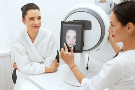 Foto de Face Skin Analyze. Cosmetologist Analyzing Woman Facial Skin At Cosmetology Clinic. High Resolution - Imagen libre de derechos