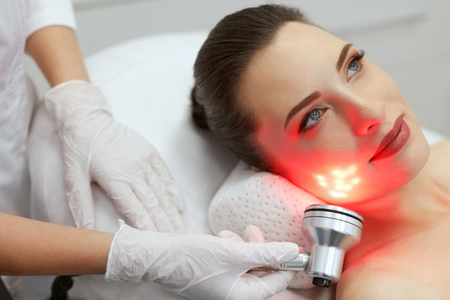 Photo pour Red Led Light Treatment. Woman Doing Facial Skin Therapy At Cosmetology Beauty Clinic. High Resolution - image libre de droit