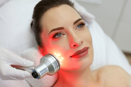 Photo pour Facial Beauty Treatment. Woman Doing Red Led Light Therapy On Face Skin At Cosmetology Center. High Resolution - image libre de droit