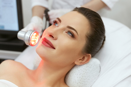 Foto de Cosmetology. Woman On Facial LED Red Light Therapy At Clinic. Cosmetologist Using Red Light For Skin Treatment. High Resolution - Imagen libre de derechos