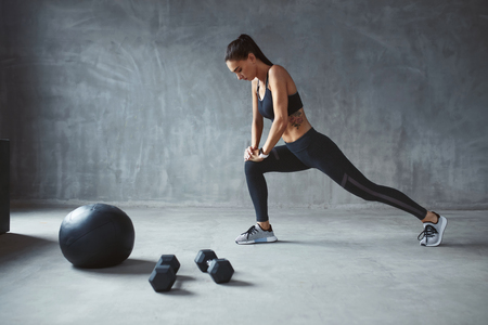 Photo pour Exercise. Sports Woman In Fashion Sportswear Stretching Legs, Training. High Resolution - image libre de droit