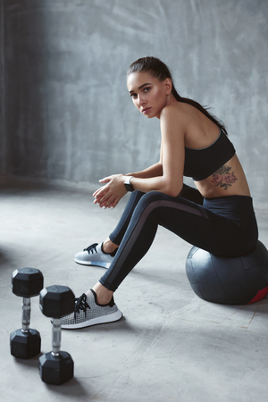 Photo pour Woman In Black Stylish Sports Wear Sitting On Fitness Ball, Fitness Training In Grey Interior. High Resolution - image libre de droit