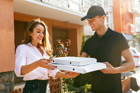 Photo pour Pizza Delivery. Courier Giving Woman Boxes With Food Outdoors. Client Receiving Order. High Resolution - image libre de droit