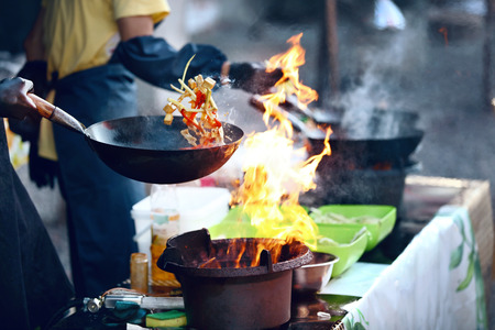 Foto de Cooking Food On Fire On Street Festival. Chef Cooking Thai Dish In Wok Outdoors. High Resolution - Imagen libre de derechos