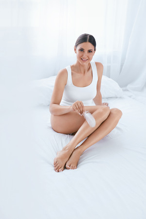 Photo pour Body Care. Woman Touching Soft Smooth Leg Skin With White Feather In Light Interior. High Resolution - image libre de droit