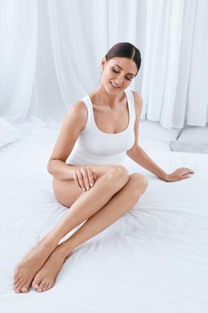 Foto de Body Skin Care. Beautiful Woman With Long Legs And Soft Smooth Skin In White Interior. High Resolution - Imagen libre de derechos