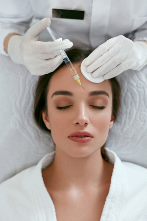Foto de Beauty Injections. Woman On Rejuvenation Procedure In Clinic, Injection Against Forehead Wrinkles. High Resolution - Imagen libre de derechos