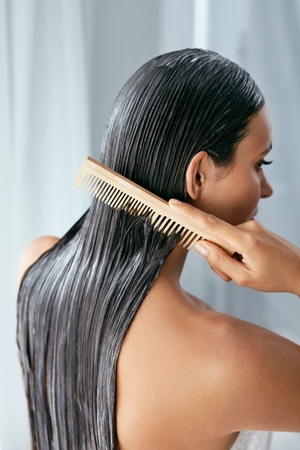 Foto de Hair Treatment. Woman With Mask On Wet Hair Closeup, Combing Hair With Wooden Hairbrush. High Resolution - Imagen libre de derechos
