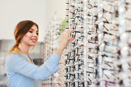 Foto de Optical Shop. Woman Near Showcase Looking For Eyeglasses, Choosing Eyewear. High Resolution - Imagen libre de derechos