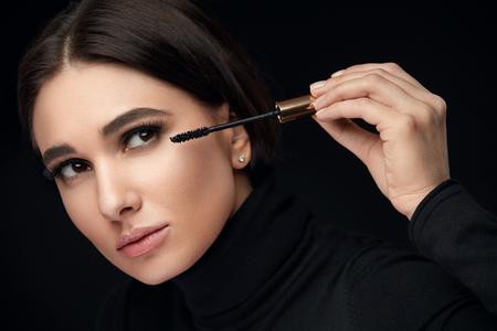 Mascara Makeup. Female Beauty Model Putting Black Mascara On Long Eyelashes With Brush. High Resolution